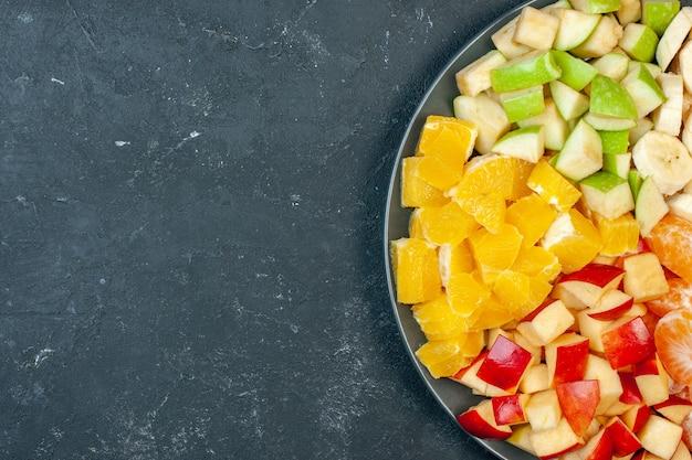 Вид сверху салат из свежих фруктов, нарезанные бананы, яблоки и апельсины на темном фоне