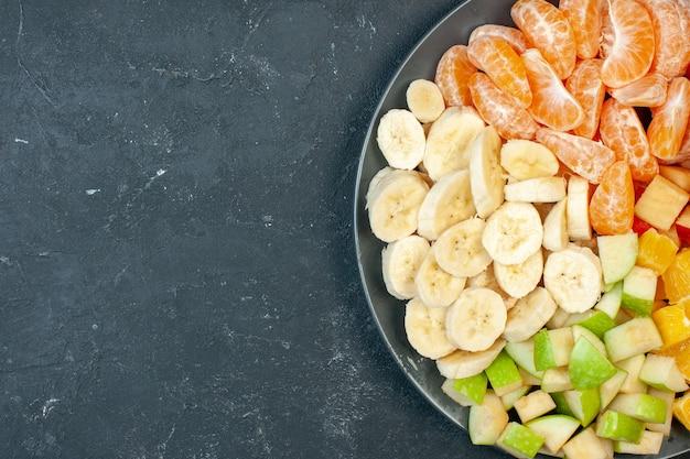 Vista dall'alto macedonia di frutta fresca banane a fette mele e arance su sfondo scuro