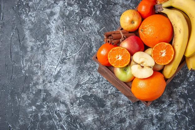 여유 공간이 있는 탁자 위의 나무 쟁반에 있는 신선한 과일과 계피 스틱
