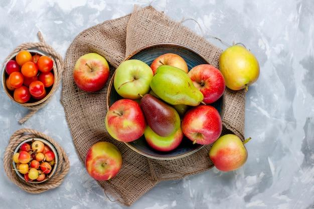 Вид сверху свежие фрукты, яблоки и манго на светлом белом столе