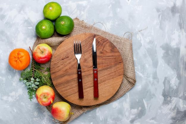 Вид сверху свежие фрукты, яблоки и мандарины на светло-белом столе