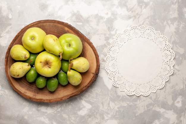 Vista dall'alto frutta fresca mele feijoa e pere su uno spazio bianco