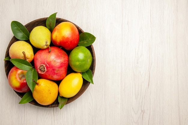 Top view fresh fruits apples pears and other fruits inside plate on a white desk fruits ripe tree color mellow many fresh