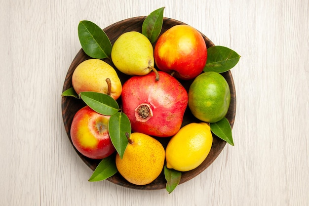 Top view fresh fruits apples pears and other fruits inside plate on white desk fruits ripe tree color mellow many fresh