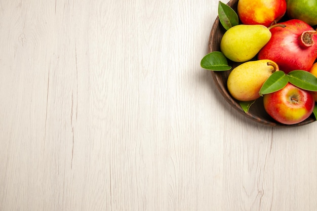 Top view fresh fruits apples pears and other fruits inside plate on a white desk fruits ripe tree mellow many fresh