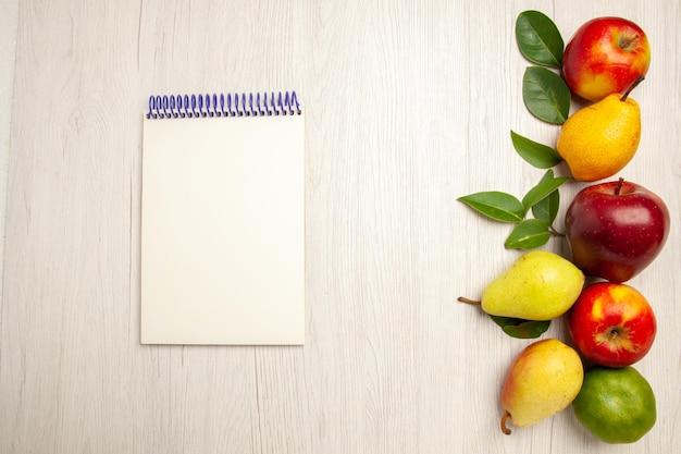 Vista dall'alto frutta fresca mele e pere su scrivania bianca frutta albero maturo colore morbido molti freschi