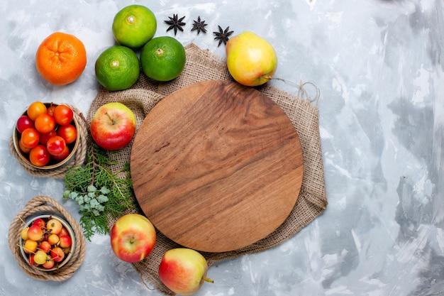 밝은 흰색 책상 위에 있는 신선한 과일 사과 자두와 감귤