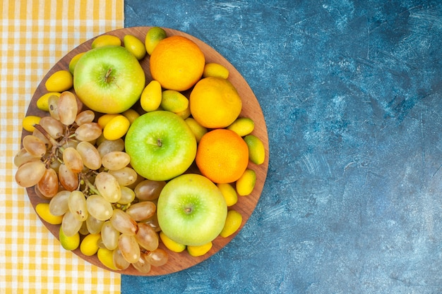 파란색 탁자에 있는 신선한 과일 사과 귤과 포도