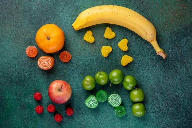 Vista superiore del mandarino e della mela della banana di frutta fresca con le caramelle della marmellata d'arance su verde scuro