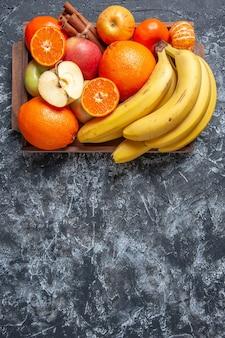 신선한 과일 바나나 사과 오렌지 계피 스틱은 여유 공간이 있는 탁자 위의 나무 쟁반에 올려져 있습니다.