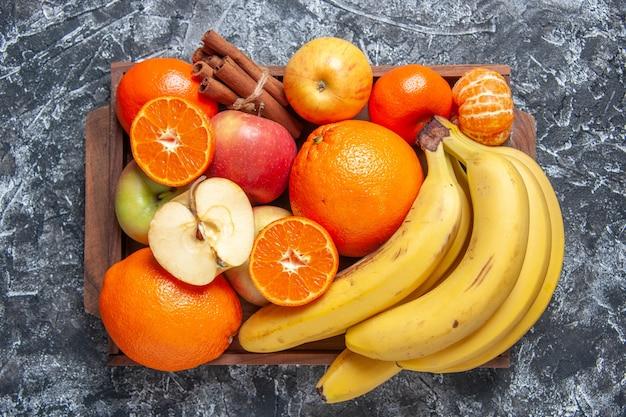 Vista dall'alto frutta fresca banane mele arance bastoncini di cannella sul vassoio di legno sul tavolo