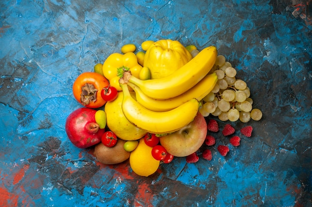 Top view fresh fruits bananas grapes and other fruits on blue background diet mellow photo health color ripe tasty