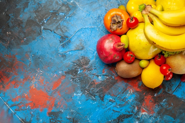 Top view fresh fruits bananas grapes and other fruits on blue desk diet mellow photo health color ripe tasty