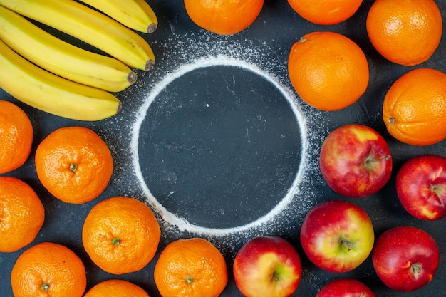 Top view fresh fruits bananas tangerines oranges and apples on dark background