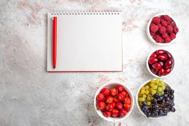 Вид сверху свежие фрукты, ягоды и виноград на белой поверхности, фруктовые ягоды, дерево, мягкая свежесть