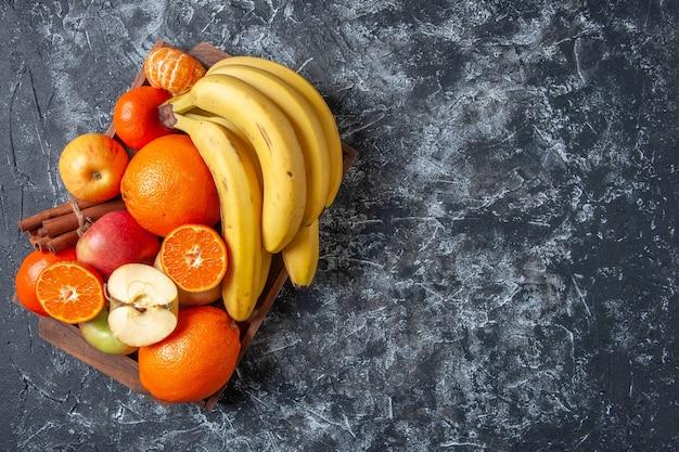 Vista dall'alto frutta fresca e bastoncini di cannella su vassoio di legno sul tavolo con spazio per le copie