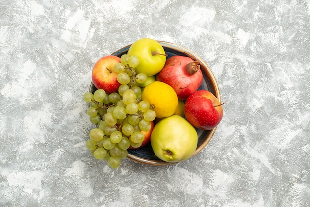 Top view fresh fruits composition apples grapes and other fruits on a white background fresh mellow fruit ripe color vitamine
