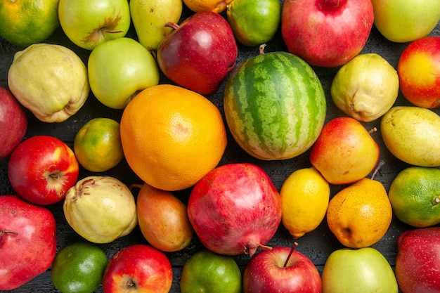 Top view fresh fruits composition apples pears and tangerines on a dark-blue desk fruit ripe tree color fresh mellow many