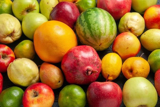 Top view fresh fruits composition apples pears and tangerines on dark-blue desk fruit ripe tree color fresh mellow many