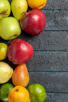 Top view fresh fruits composition apples pears and tangerines on a dark-blue desk fruits ripe tree color mellow many fresh