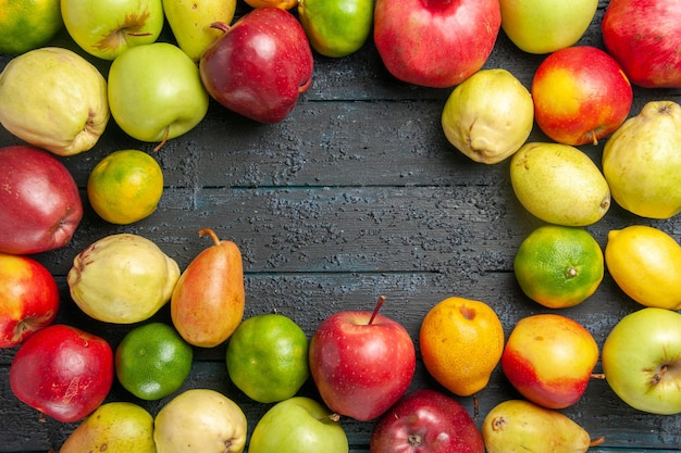 Top view fresh fruits composition apples pears and tangerines on dark-blue desk fruits ripe tree color mellow many fresh