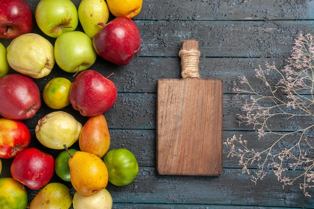 Top view fresh fruits composition apples pears and tangerines on dark blue desk fruits ripe tree color mellow many fresh