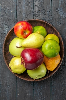 Top view fresh fruits composition apples pears and tangerines inside plate on a dark-blue desk fruit color fresh ripe mellow tree