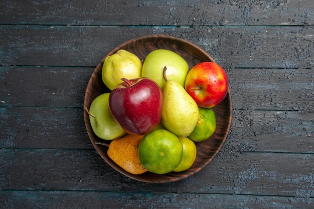 Top view fresh fruits composition apples pears and tangerines inside plate on dark-blue desk fruit color fresh ripe mellow tree