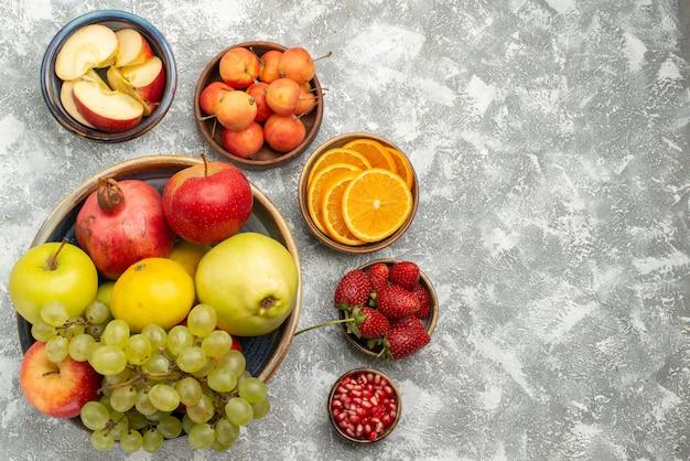 Vista dall'alto composizione di frutta fresca mele prugne uva e altri frutti su sfondo bianco frutta fresca e pastosa vitamina matura