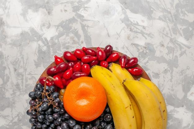 Vista dall'alto composizione di frutta fresca banane cornioli e uva sulla superficie bianca frutta bacca freschezza vitamina