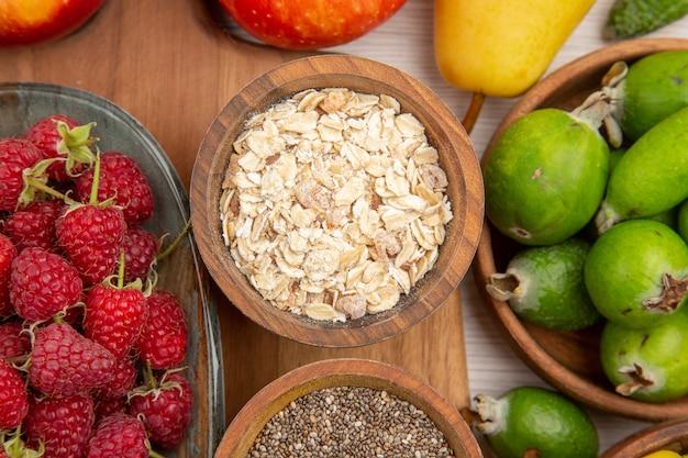 Вид сверху свежие фрукты композиция разных фруктов со злаками на белом фоне