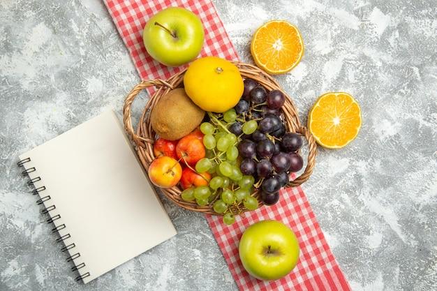 Vista dall'alto composizione di frutta fresca uva e prugne con fette di arancia su sfondo bianco vitamina frutta matura fresca dolce