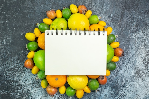 Top view fresh fruits composition lemons feijoa and tangerines on the gray background