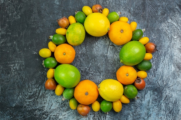 Top view fresh fruits composition lemons feijoa and tangerines on grey background