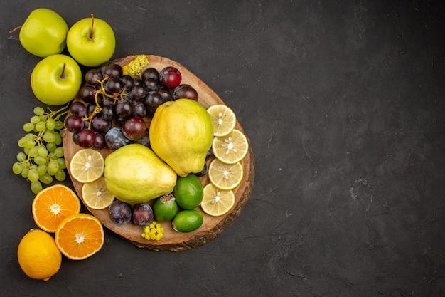 上面図新鮮な果物の組成は、暗い表面でまろやかで熟している果物熟したまろやかな健康新鮮