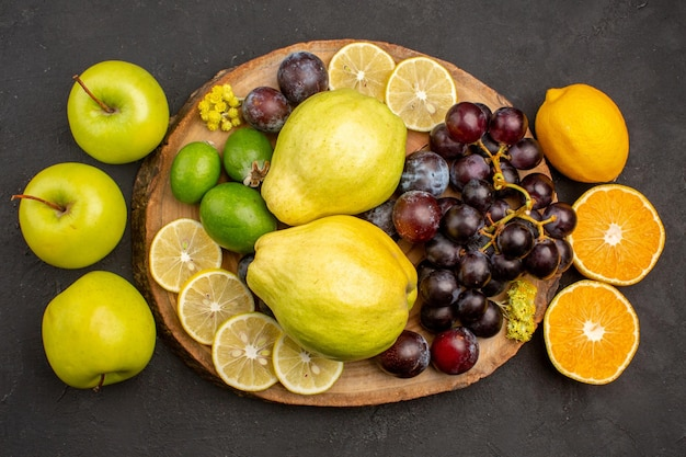 Top view fresh fruits composition mellow and ripe fruits on a dark surface