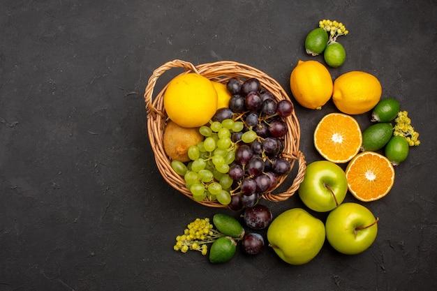 Vista dall'alto composizione di frutta fresca frutta affettata e matura dolce sulla scrivania scura frutta vitamina fresca dolce matura