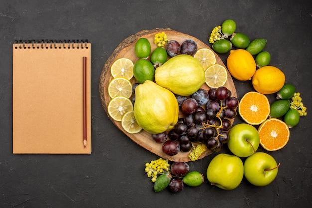 Vista dall'alto composizione di frutta fresca dolce affettato e frutti maturi su superficie scura frutta fresca matura vitamina dolce
