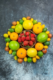 Top view fresh fruits composition with red strawberries on grey background