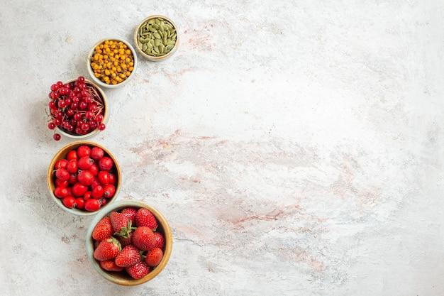 上面図新鮮な果物白いテーブルの上のさまざまなベリーフルーツベリーの新鮮な味