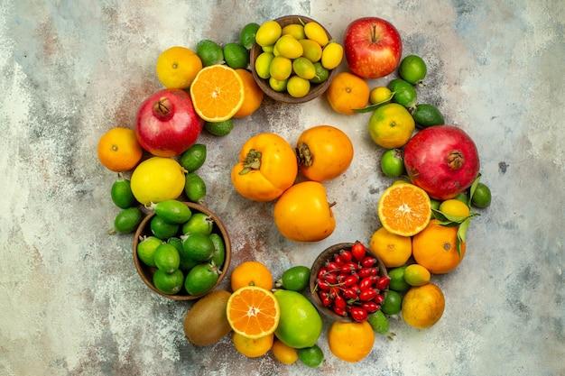 Вид сверху свежие фрукты разные спелые фрукты на белом фоне дерево здоровья цветное фото ягоды цитрусовые спелые вкусно