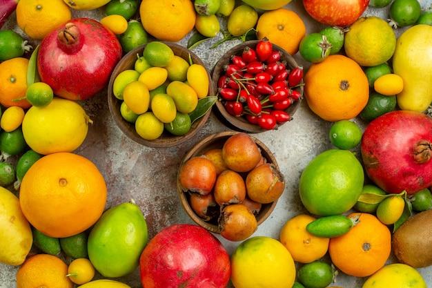 Вид сверху свежие фрукты разные спелые фрукты на белом фоне диета вкусная ягода цветная фото здоровье спелое дерево