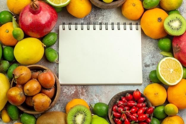 Вид сверху свежие фрукты разные спелые фрукты на белом фоне вкусные фото спелые ягоды диета цвет дерева здоровье