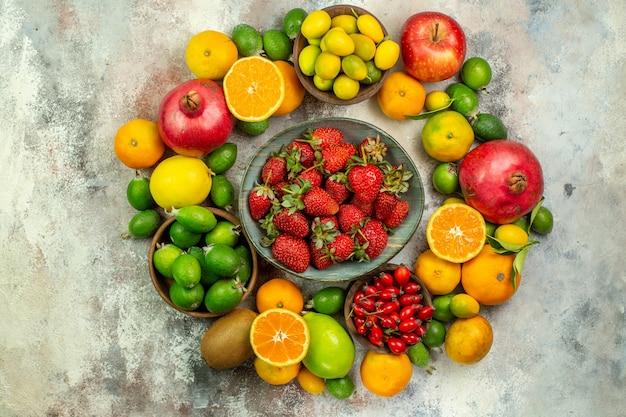 Вид сверху свежие фрукты разные спелые фрукты на белом фоне цвет здоровья вкусные спелые ягоды цитрусовые
