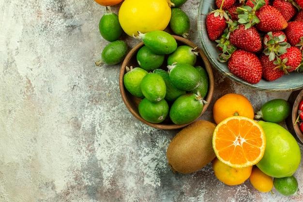 Вид сверху свежие фрукты разные спелые фрукты на белом фоне цвет дерева здоровья вкусные ягоды цитрусовые спелые