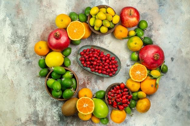 上面図新鮮な果物白い背景の上のさまざまなまろやかな果物健康ツリー色おいしい熟したベリー柑橘類