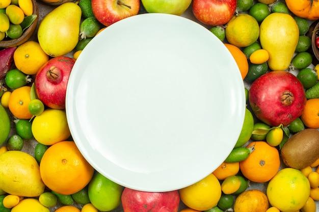 Вид сверху свежие фрукты разные спелые фрукты на белом фоне спелые ягоды диета вкусный цвет дерева здоровья