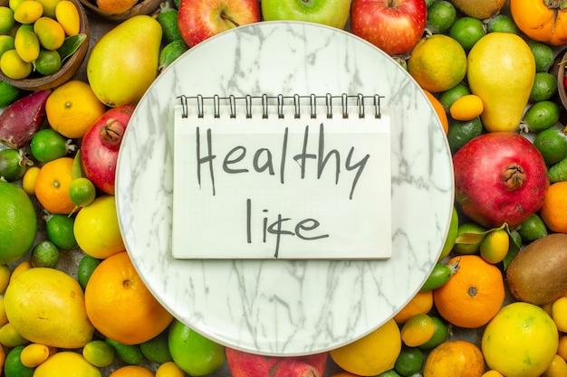 Vista dall'alto frutta fresca diversi frutti dolci su sfondo bianco dieta bacche colore gustoso vita sana albero maturo ripe