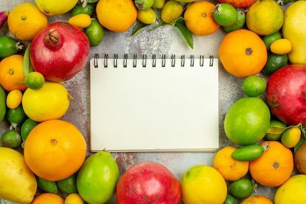 Vista dall'alto frutta fresca diversi frutti dolci su sfondo bianco dieta gustosa bacca colore salute albero maturo