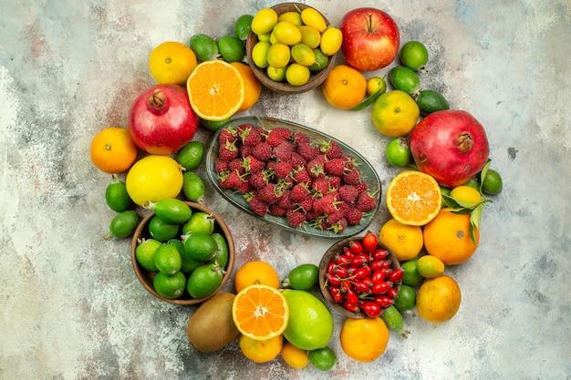 Vista dall'alto frutta fresca diversi frutti dolci sullo sfondo bianco colore dell'albero della salute foto gustosa bacche mature agrumi